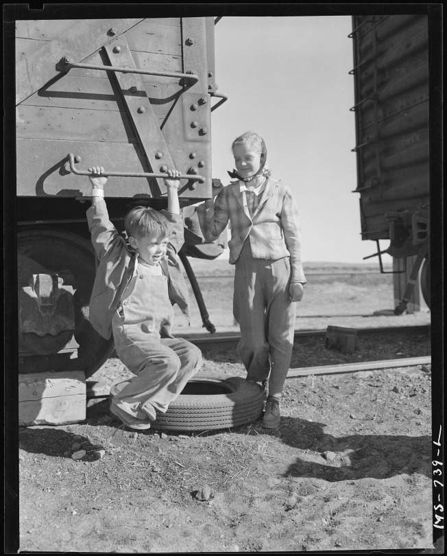 Child_of_miner_swinging_on_box_car_home_of_company_housing_project._Union_Pacific_Coal_Company,_Reliance_Mine..._-_NARA_-_540577