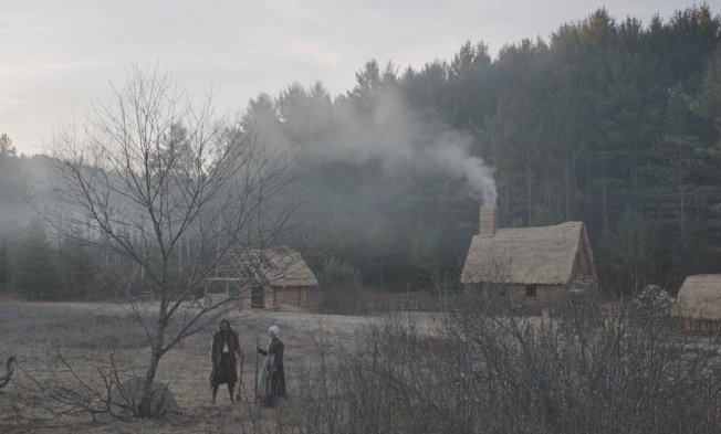 witch-the-2015-001-couple-in-foreground-of-wide-shot-smoking-house-in-front-of-forest.jpg