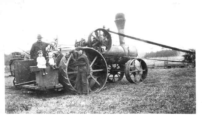 Steam engine with  Duncan on tractor, Lawrence standing beside it Edith and Lloyd sitting on the wheelBW.jpg